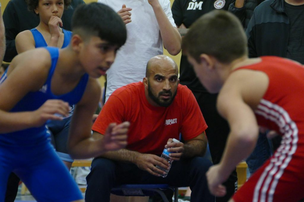 Coach Farid looks on at a junior wrestling competition